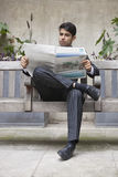 Young Indian businessman reading newspaper while sitting on bench Stock Images
