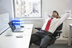 Young Indian businessman relaxing in chair at office desk Stock Photos