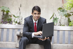 Young Indian businessman using laptop while sitting on bench Stock Image