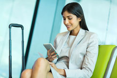 Young indian businesswoman. Attractive young indian businesswoman using smart phone at airport Stock Photos