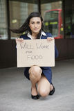 Young Indian businesswoman holding 'Will Work for Food' sign Stock Image