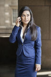 Young Indian businesswoman looking away while using cell phone Stock Image