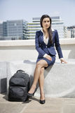 Young Indian businesswoman with luggage sitting outdoors Stock Images