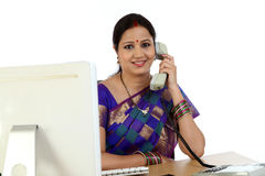 Young Indian businesswoman talking on telephone. At her desk Royalty Free Stock Photos