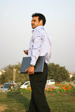 Young indian ceo. Young indian walking with laptop and mp3 player in the park Royalty Free Stock Images