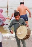 Work is worship - Small child playing drum to earn money Royalty Free Stock Image