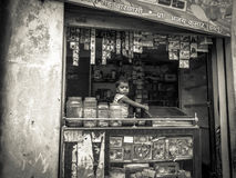 Young Indian child in a shop window. A young Indian child sits in a shop window in a rural situation. Poverty and illiteracy are rife in rural India Stock Photography