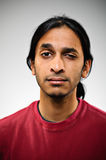 Young Indian ethnic man with raised eyebrow. A young Indian man blank expression portrait Stock Photo