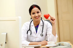 Young Indian female doctor holding red heart shape Stock Photography