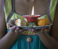 Young Indian Female dressed in traditional clothes Carrying Indian Diwali Sweets Stock Images
