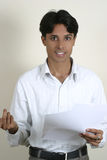 Young indian gesturing with hands. Smart young indian gesturing with papers in hands Royalty Free Stock Image