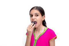 Young indian girl eating a gulab jamun - an indian sweet Royalty Free Stock Image