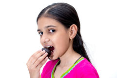 Young indian girl eating a gulab jamun - an indian sweet Stock Photos