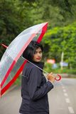Young Indian girl with short hair holding a transparent umbrella and looking back, Pune royalty free stock images