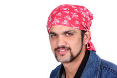 Young Indian Guy. A portrait of a stylish handsome Indian guy wearing a pirates headgear, on white studio background Stock Photos
