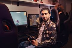 A young Indian guy wearing a military shirt sitting on a gamer chair and looking at a camera in a gaming club or. A Indian guy wearing a military shirt sitting royalty free stock photo