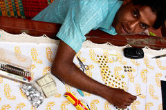 Young indian man is embroidering. Royalty Free Stock Images