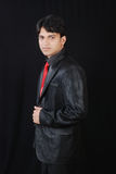 Young indian man looking with confidance. A portrait of young indian man standing in side pose wearing black suit Stock Photography