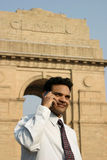 Young indian on mobile phone. Young indian businessman talking on mobile with a backdrop of famous india gate in delhi, india Royalty Free Stock Photos
