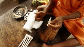 Young indian monk shows wicks from cotton speaks something top view