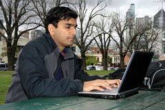 Young Indian student outside the college campus. Young Indian student working on his laptop outside the college campus Royalty Free Stock Photography