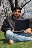 Young Indian student outside the college campus. Young Indian student working on his laptop outside the college campus Stock Images