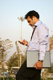 Young indian using mp3 player. Young indian walking with laptop and listening to musicmp3 player in the park Stock Image