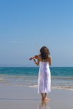 Young indian violin player on beach Stock Image