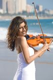 Young indian violin player on beach Royalty Free Stock Photo