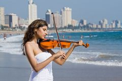 Young indian violin player on beach Stock Photo