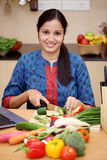 Young Indian woman cutting vegetables Stock Photo