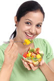 Young Indian woman eating fruit salad against white Royalty Free Stock Photography