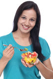 Young Indian woman eating fruit salad Stock Images