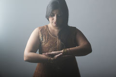 Young indian woman embracing her ethnicity. With hands together isolated on grey backgroud Royalty Free Stock Images