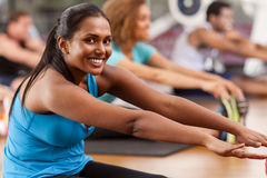 Young Indian woman in a gym. Young Indian women stretching in a gym and looking to camera Royalty Free Stock Images