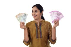 Young Indian woman holding currency notes agianst white Royalty Free Stock Images