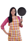Young Indian woman holding kitchen utensil against white Royalty Free Stock Image