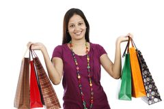 Young Indian woman holding shopping bags. Happy young Indian woman holding shopping bags isolated on white background Royalty Free Stock Images