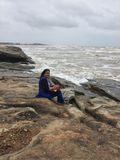 A young Indian woman posing on rocky shores of Kundapura. During a trip Royalty Free Stock Photography
