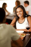 Young Indian woman in a restaurant. Beautiful young Indian woman smiling at her partner in a restaurant Royalty Free Stock Photography