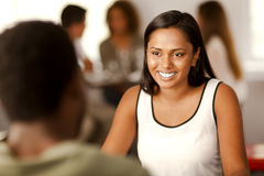 Young Indian woman in a restaurant. Beautiful young Indian woman smiling at her partner in a restaurant Stock Photo