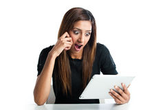 Young Indian woman shocked at tablet computer. Stock Photo