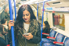 Young indian woman using smart phone in the tube. Young indian woman looking at her smart phone and typing while travelling on the tube in London. She is Royalty Free Stock Image