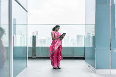 Young Indian woman using a tablet Pc on a terrace in a windy day royalty free stock photography