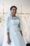 Young indian woman in wedding dress with bridal gowns on display. In boutique Royalty Free Stock Photography