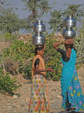 Young Indian women carry pots of water Stock Photos