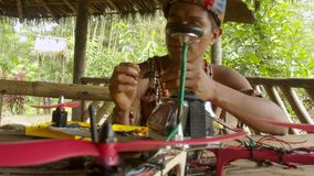 Young indigenous man is trying to build his own drone. Young, indigenous man is trying to build his own drone he is checking its components medium shot, slow stock video footage