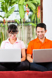 Asian couple on the couch with a laptop. Young Indonesian couple sitting with laptops on a couch, maybe the have an idea or inspiration Stock Photos