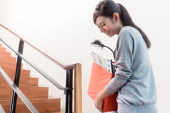 Young Indonesian girl carrying removal crate up the stairs. Young Indonesian girl carrying moving boxes up the stairs Royalty Free Stock Photos