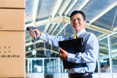Young Indonesian Man in warehouse with Scanner. Young Indonesian man in a suit with a bar code scanner in a Asian warehouse Royalty Free Stock Photos